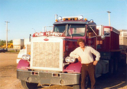old pic of a man standing beside a truck